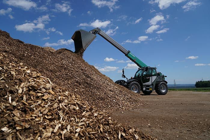 Kramer KT429 telehandler agriculture with bucket at a pile with wood chips